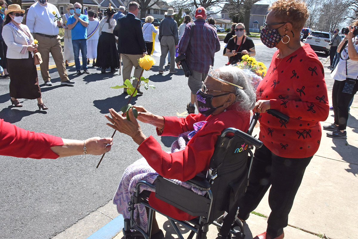 Someone hands a yellow rose to Mabel Hart, sitting in a wheelchair on the sidewalk