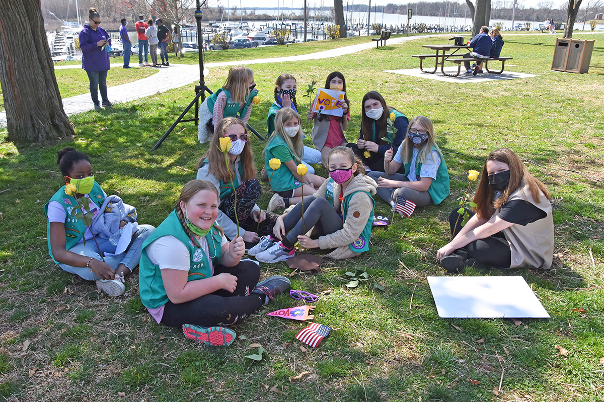 Girl Scouts sitting on grass, some holding yellow roses and looking at camera