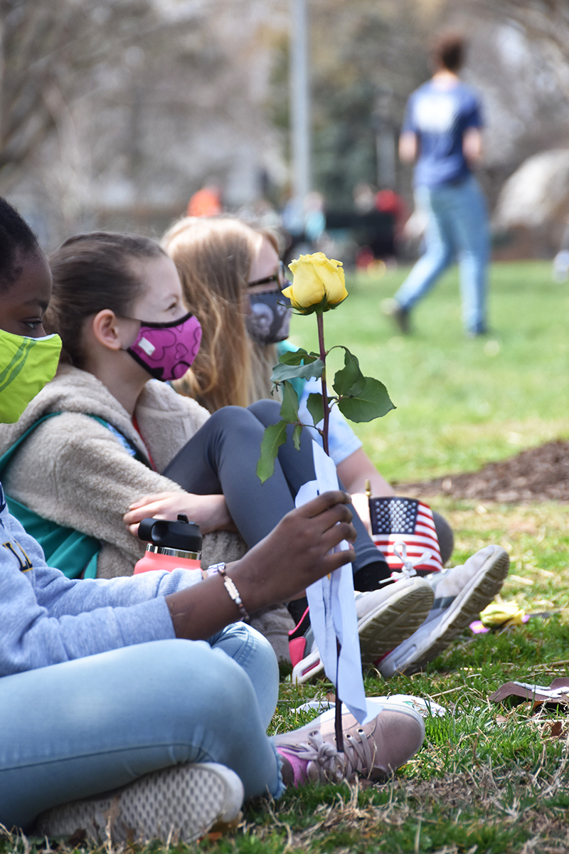 Young girls sitting on grass, one holding a rose.