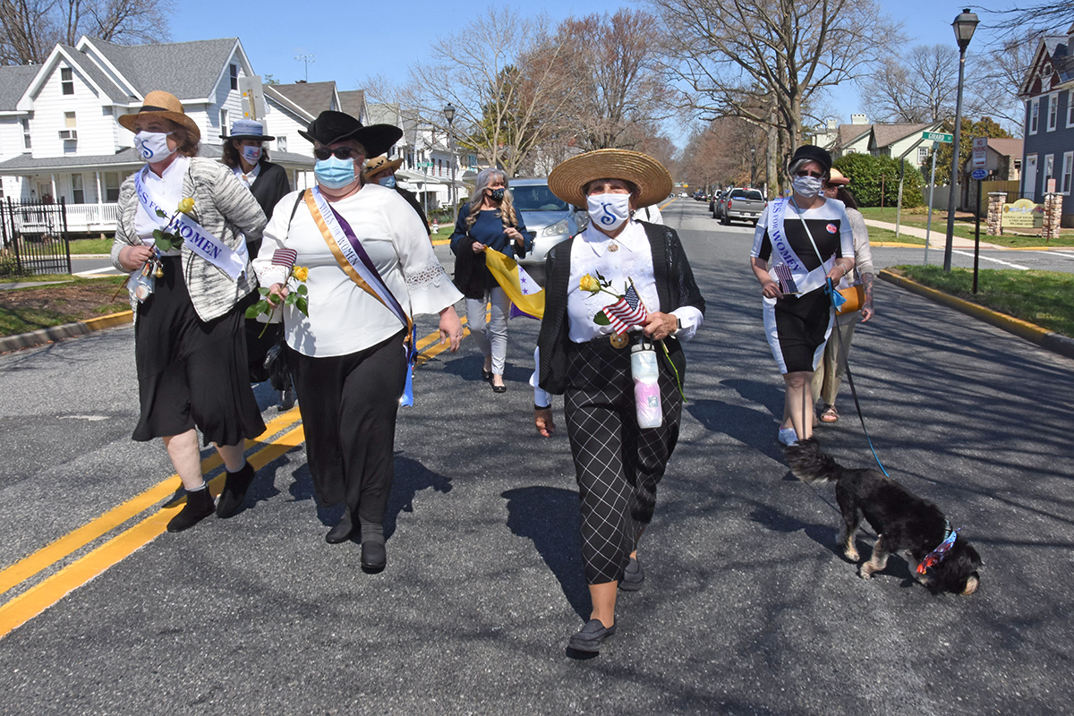 Four women dressed in black and white, one walking a dog, att he end of the parade.