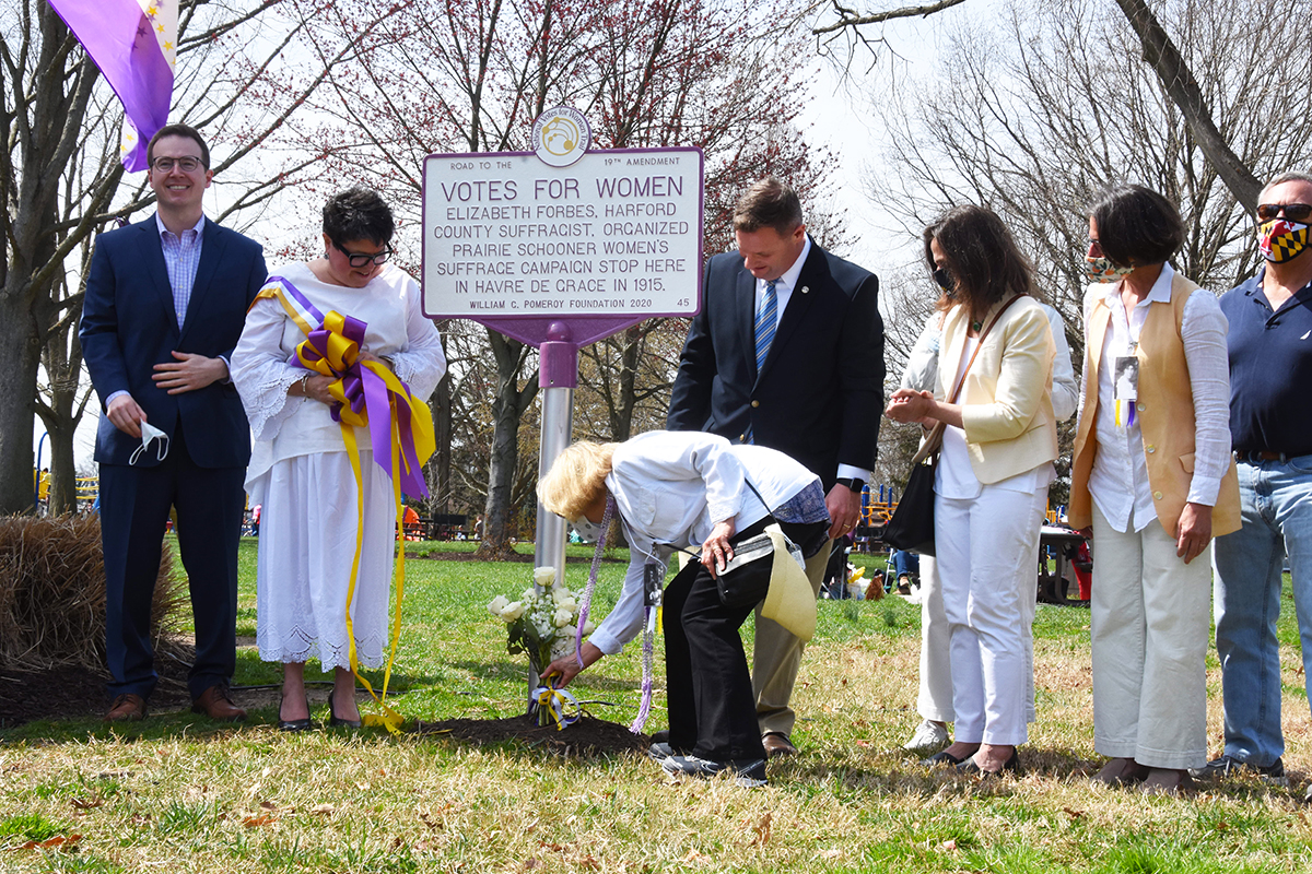 A Forbes descendent places flowers at the base of the marker