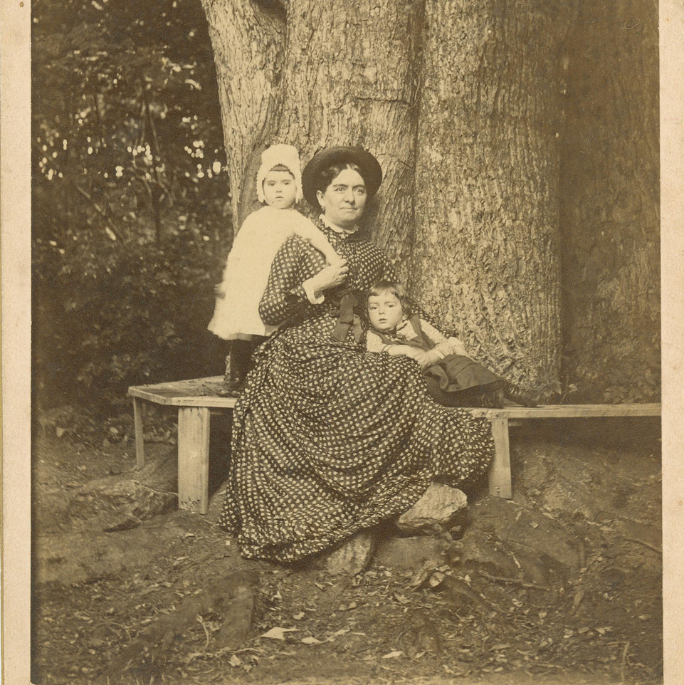 Mary Bentley Thomas sitting on a bench in front of a tree