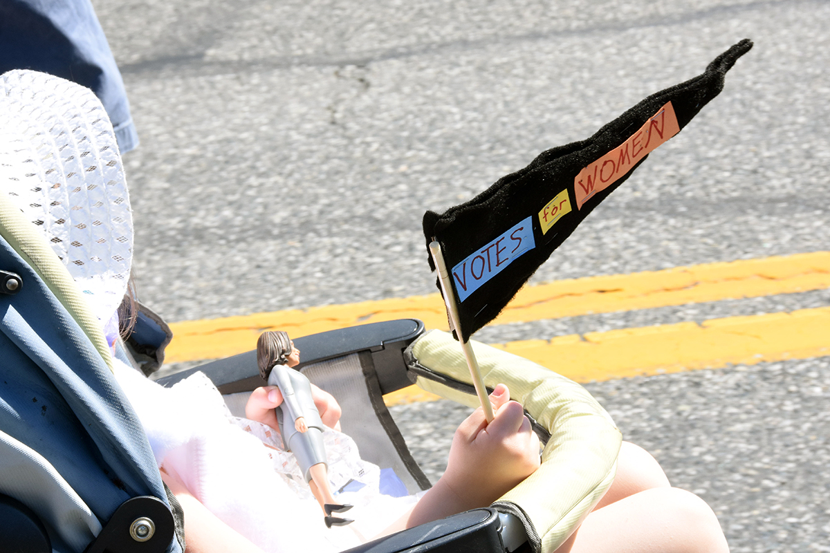 A side shot of a child in a stroller carrying a homemade votes for women flag and a Kamala Harris doll