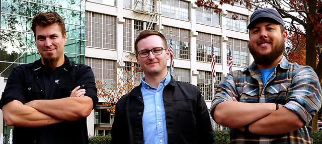The AV Department video production team standing outside in front of a building. Three people are shown.