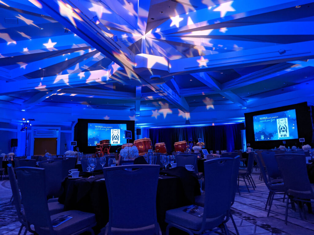 ballroom set with blue lighting and stars projected on the ceiling
