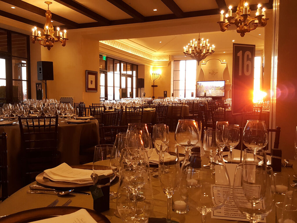 tables are set for a special event dinner. it is sunset and a beam of light is coming through the window