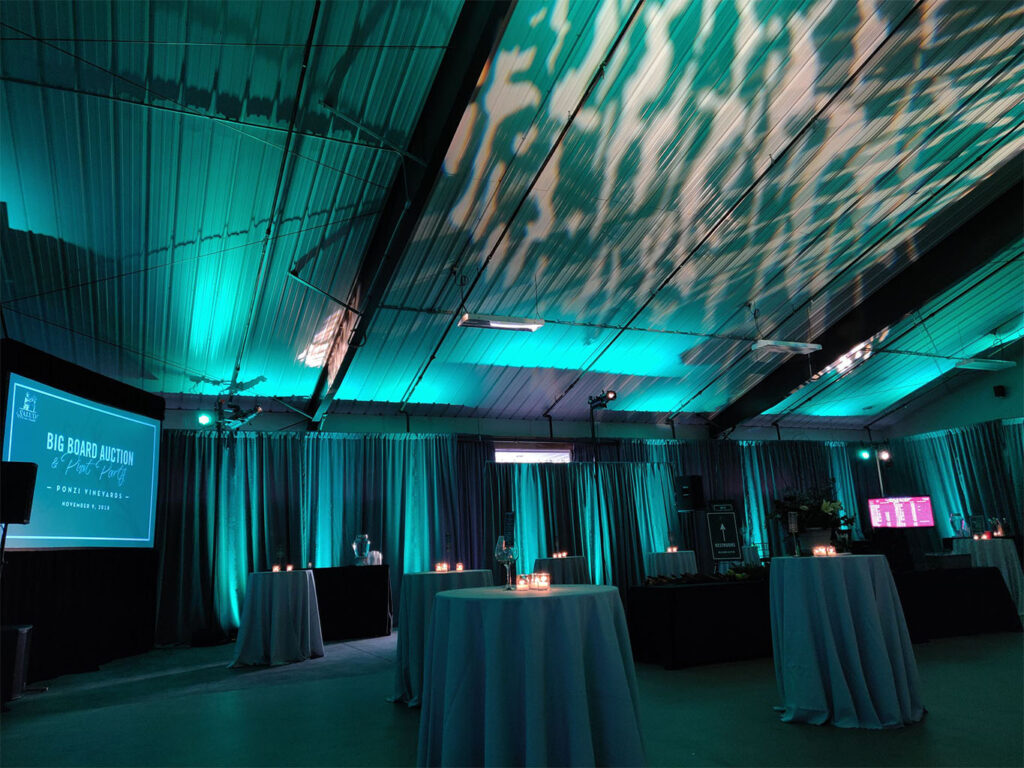Oregon winery set for special event with tables and dim lighting and a large screen