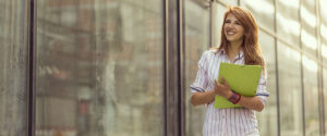 a smiling woman holding a notebook walks along the outside of a building