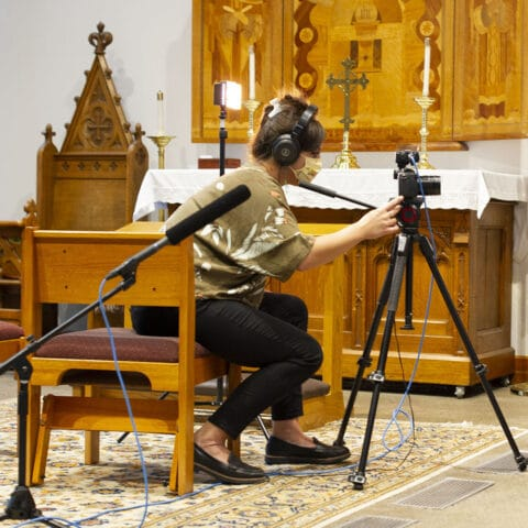 A videographer films in a chapel