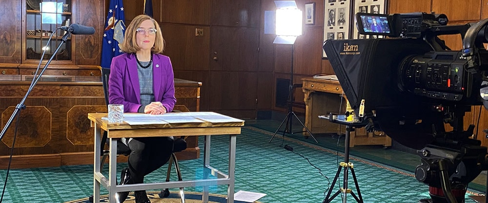 Oregon's Governor Kate Brown is shown sitting behind a table facing a camera during a virtual press conference.