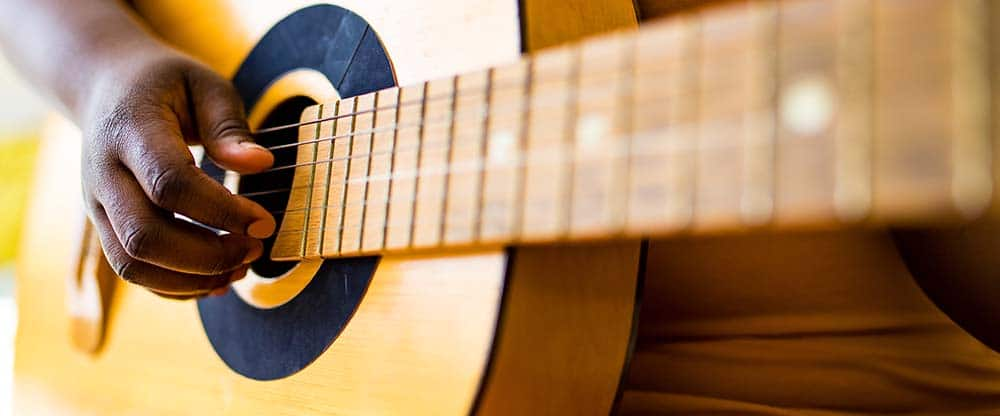 A person playing guitar. Secure a music license for virtual events and video entertainment