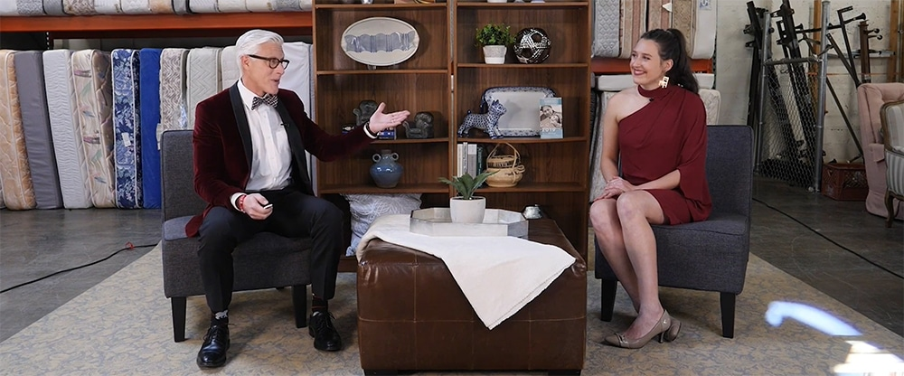 two people in formal attire are seated in a storage area at a nonprofit furniture bank. There is a bookcase with household items on shelves behind them with mattresses stored against a back wall. The video opened the virtual event for Community Warehouse.