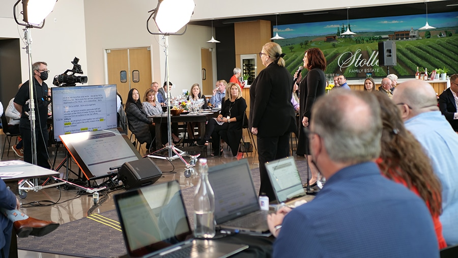 Two people host a hybrid event. Between them and the in-person audience are large lights, a camera and two large monitors. Behind and to the side of the hosts are three people on laptops managing the script and online bidding