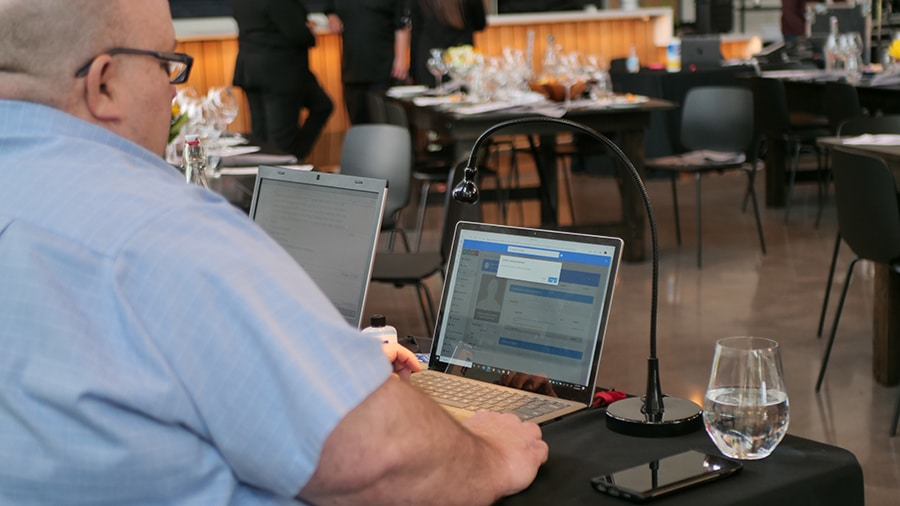An event strategist monitors online bidding during a hybrd event