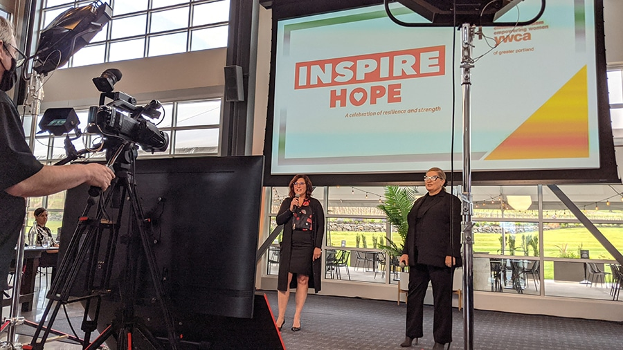 Two event hosts stand in front of a camera, lights, and monitors during a hybrid event.