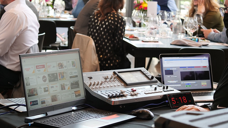 Equipment to run a slide presentation during a hybrid event is set up on a table. Event attendees are at tables in the background