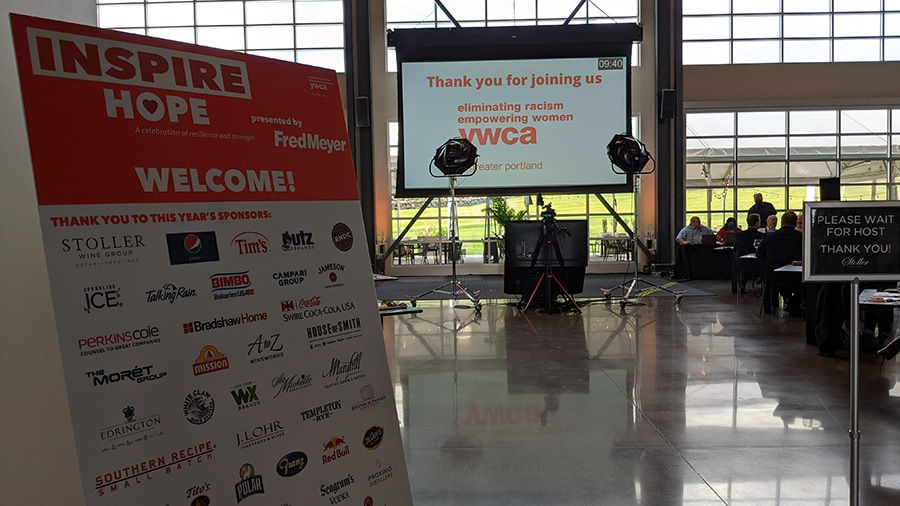 At the entrance to a large event space is placed a welcome sign thanking even sponsors. The event space has a wall of windows ad overlooks a large green lawn.