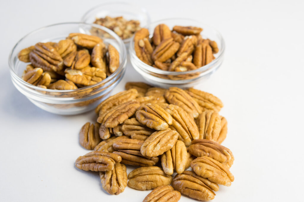 Pile of pecans next to some small dishes of pecans