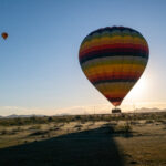 Hot air balloon crossing in front of the setting sun