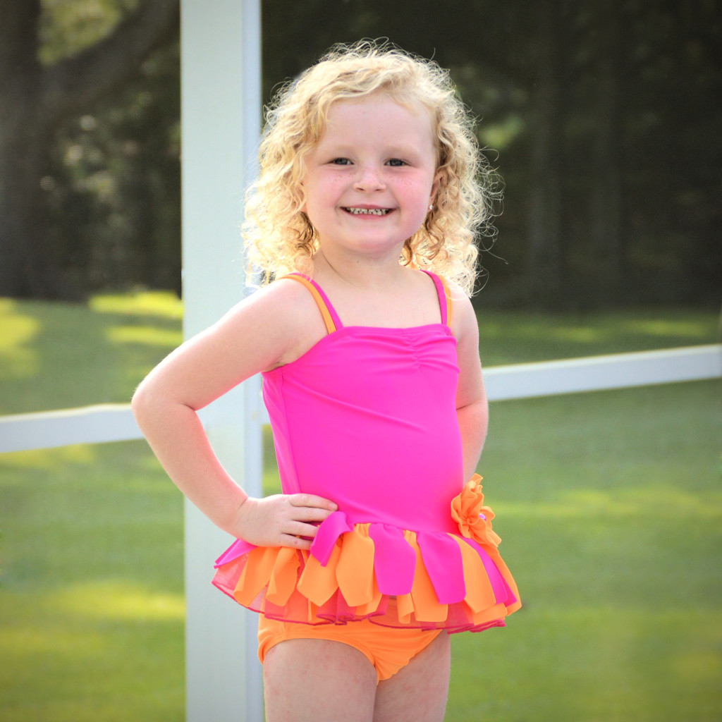 AnnaLane is wearing our Sunburst tankini set, style 8698NFA, available in sizes 3M-6X.