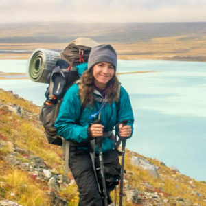 Jessica Weinberg McClosky on a hillside above a turquoise lake