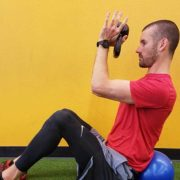 Personal trainer performing v-sit overhead reach in Vancouver, WA