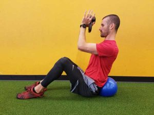 Vancouver, WA personal trainer performing v-sit overhead reach