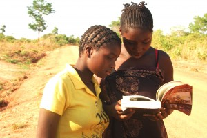 """Two girls browsing the only copy  the author had of the book: """"Satisfying Zambian Hunger for Culture"""". This was in November 2012 at Chikana Village in Chief Magodi's area  West of Lundazi."""