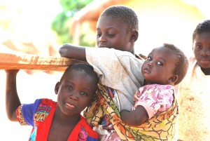 Girl carrying her baby sister on the her back. Her back is small enough for the baby to feel comfortable. This was in a village in Zambia.