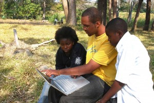 My son Sekani Tembo who was a Third year computer major in at an American College showing his cousins, Abiudi and Nina, a lap top computer behind the Castle Hotel in Lundazi in 2009.