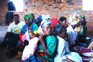 An 8 year old child sits next to the women attending a meeting of the construction of the Nkhanga Village Library in June 2009