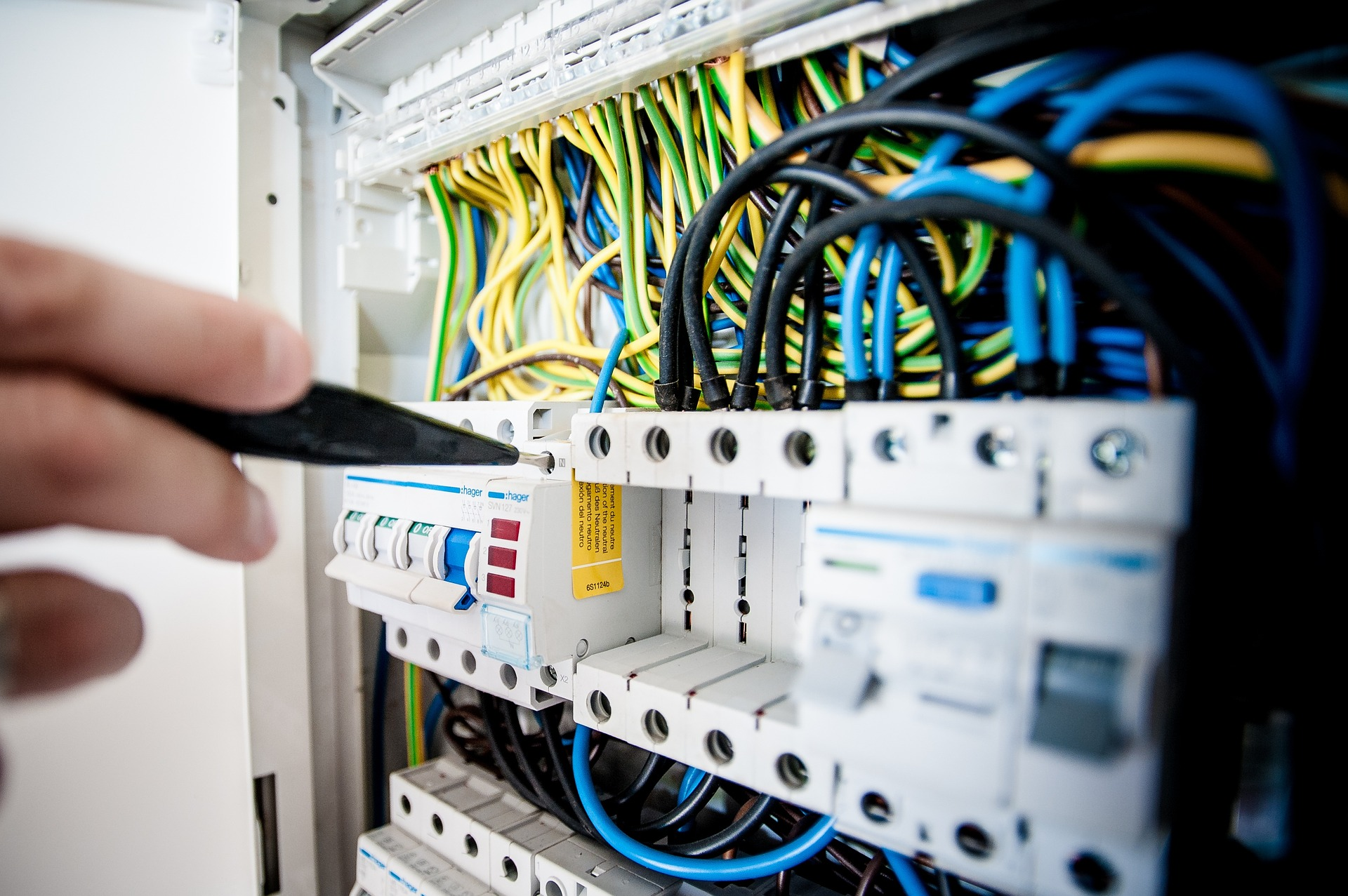 A hand working on a rack of Voice and Data Cabling