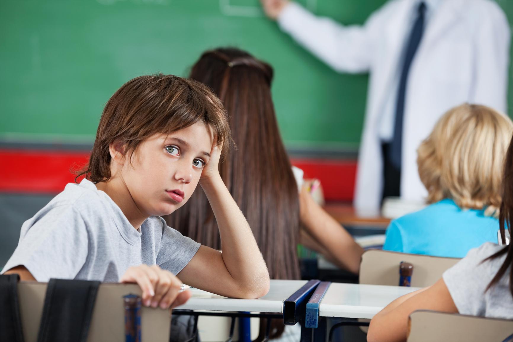 Portrait Of Little Boy Leaning At Desk