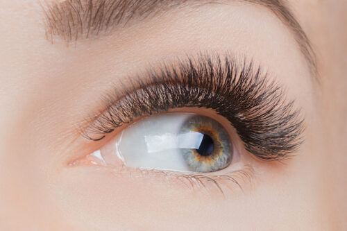 Macro photo woman with long lashes in beauty salon. Concept eyelash extension procedure.