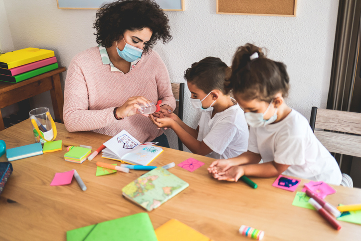 teacher doing activities with children at table, top daycare franchises