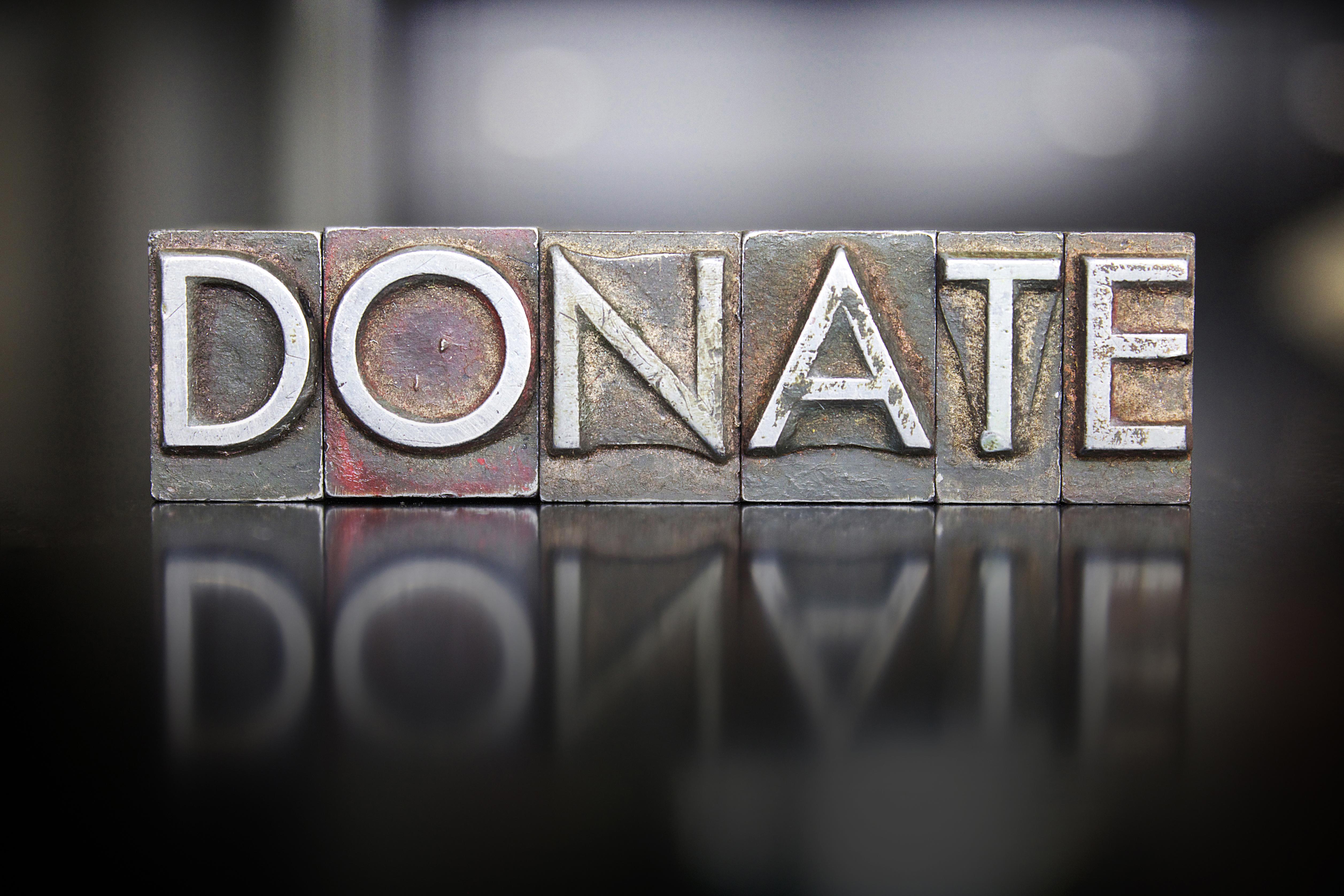 The word DONATE written in vintage letterpress type
