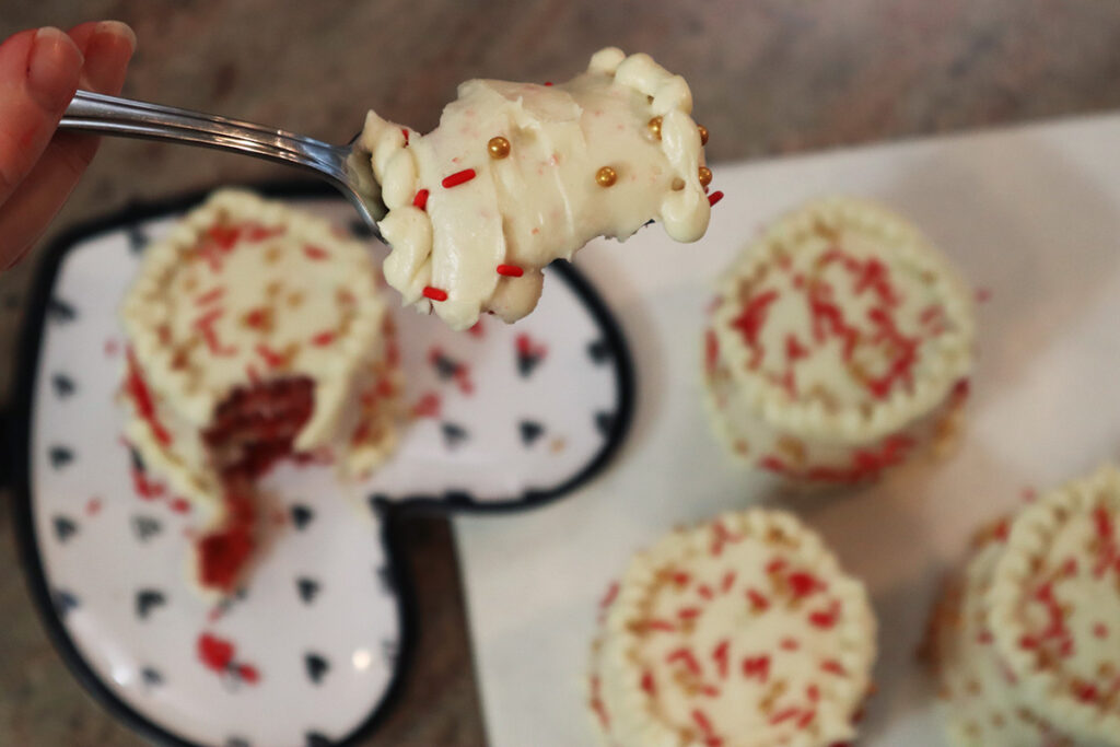 piece of red velvet cake showing cream cheese frosting