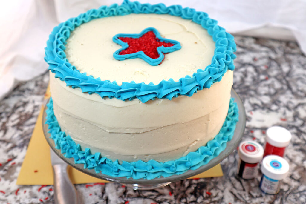 Frosted Round Cake with White Blue and a Red Star on Top