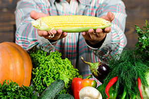 Farm stand worker presents an ear of corn