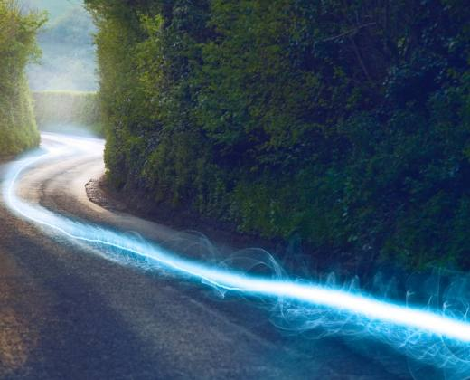 photo of streaking blue light going down a country road. Used as an icon for broadband services.