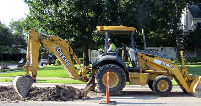 This is a photograph of a backhoe digging up a section of a street. It is used to illustrate the blog post discussing the legal requirements to call Tri-County Electric before you dig.