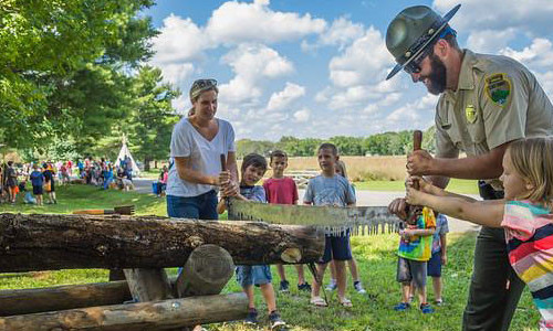 This is a photograph of a Tennessee Parks Ranger operating a hand saw with the help of some chidren and an adult woman at what looks to be a children's education event in the park. It is used to illustrate Standing Stone State Park's information about Going Green.