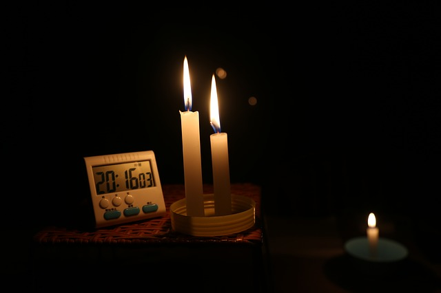 Power outage FEMA advice. This is a photo of three lit candles and a battery operated digital clock. It is used to illustrate power outages.
