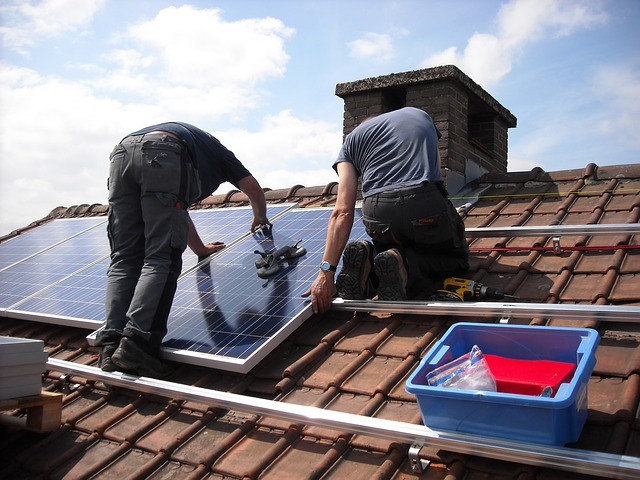 This is a photograph of two men on a roof installing solar panels. It is used to illustrate the TVA Solar Panel program.