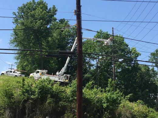 This is a photo of a TCE bucket truck with a lineman working on an utility pole connection. It is used on the site to illustrate the blog post that explains the law and the need to keep utility poles clear of all debris.