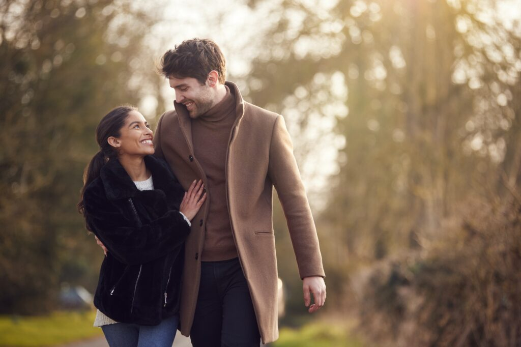 Loving Young Couple Walking Through Winter Countryside Together