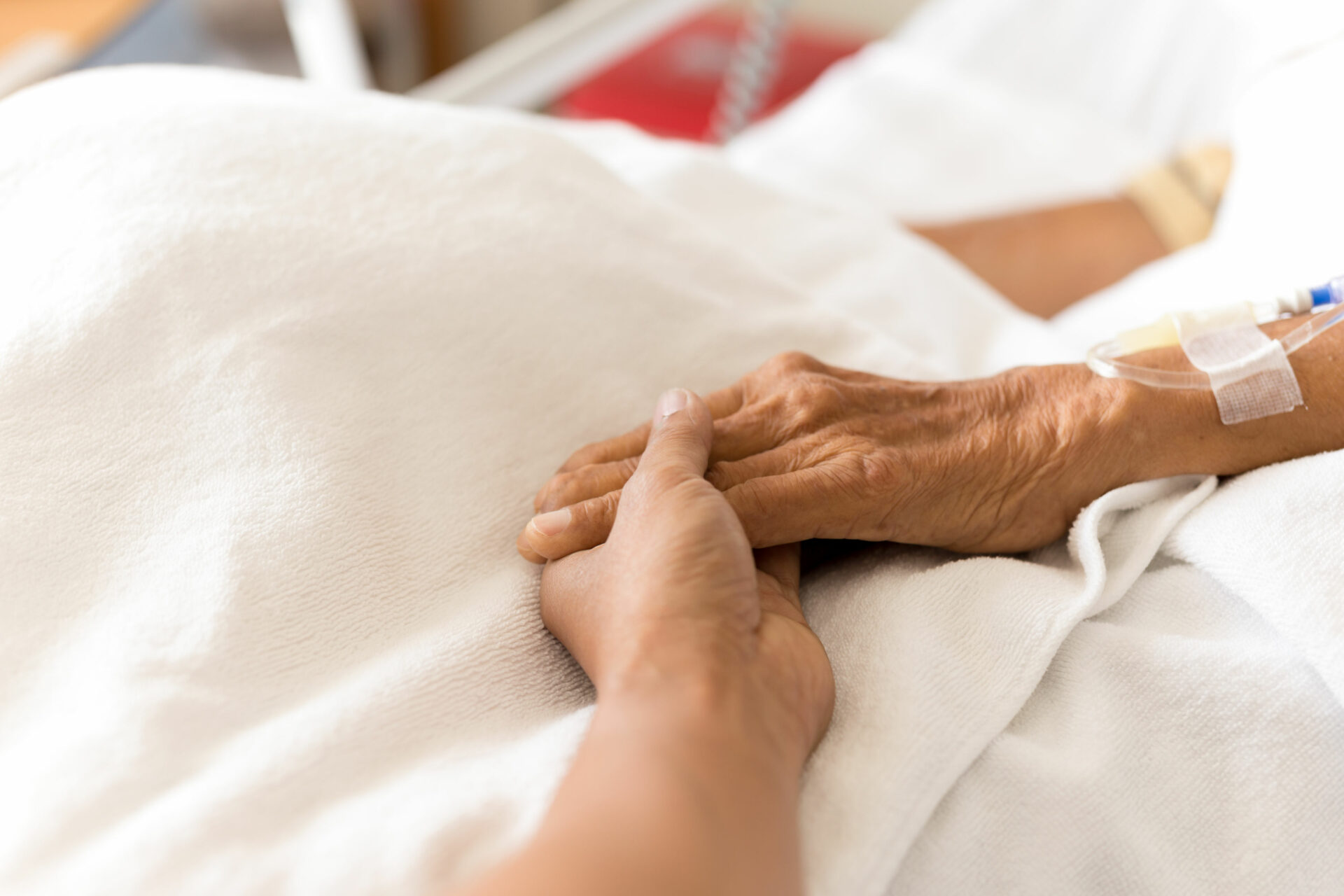94498799 - son holding father is hand with saline intravenous in the hospital room