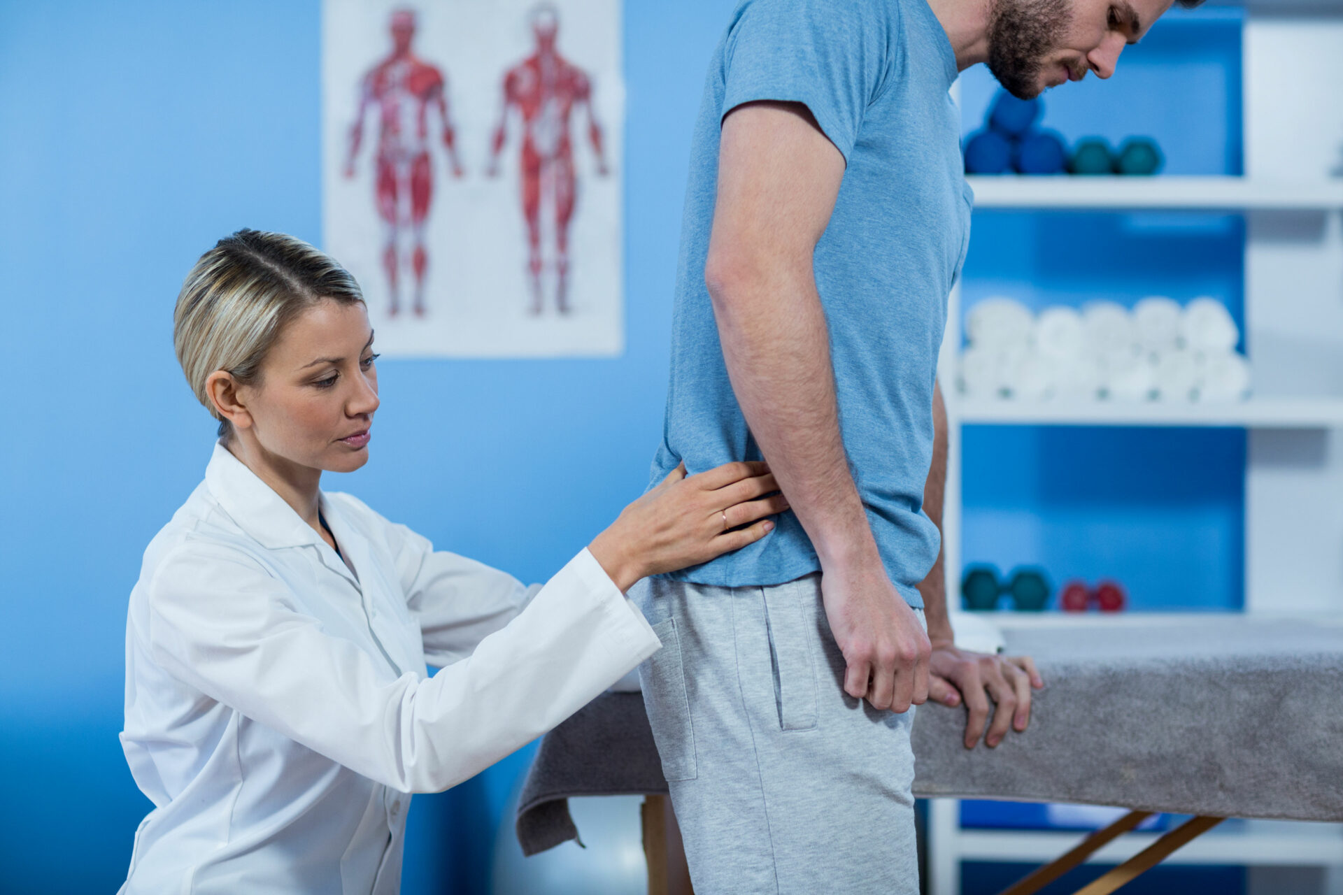 61653498 - physiotherapist examining mans back in clinic