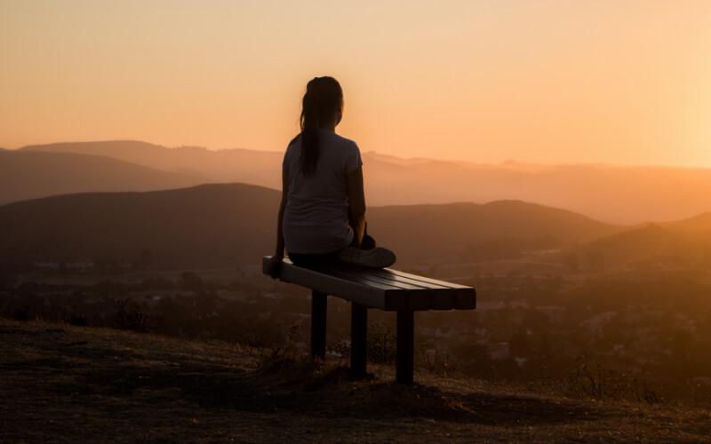 Teenage Girl Sitting on a Bench at Sunset Time