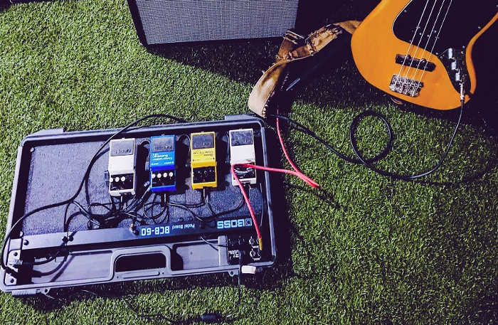 Shows a bunch of cables connected to a bass and a bunch of stompbox effects
